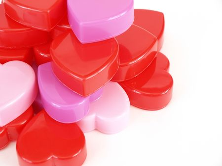 plastic heart: Plastic heart shapes in red, pink and lavendar, stacked up over a white background.