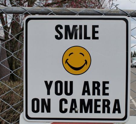 tresspass: A fence sign with a yellow smiley face alerts the public of video surveillance.