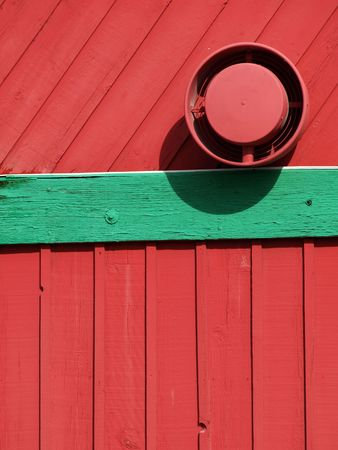 exhaust fan: A red wood sided building with green painted trim. Exterior shot showing an exhaust fan. Stock Photo