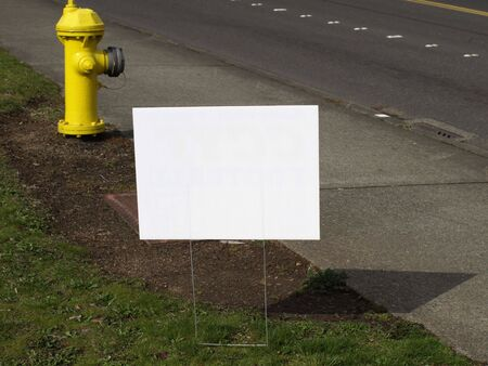 A blank white sign on the side of the road.