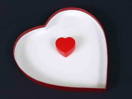 plastic heart: A red plastic heart sits alone inside a white heart shaped box over a black background.