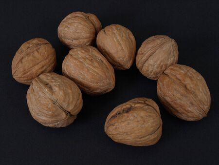 Several walnuts in shells isolated against a black background.