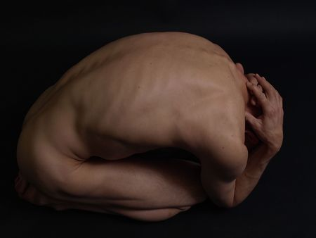 A nude male curled up into a ball on a black background.