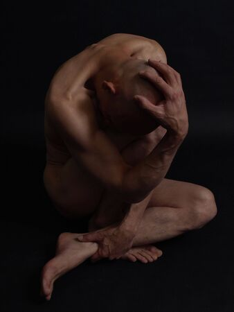 A bald nude male sits twisted and knotted, his head in his hand. Over a black background. Stock Photo