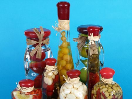 A colorful assortment of pickled spices in different shaped jars on a blue background. Reklamní fotografie