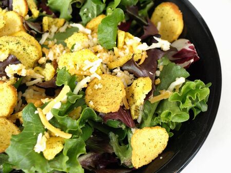 A tasty fresh greens salad with crutons and cheese in a black bowl.