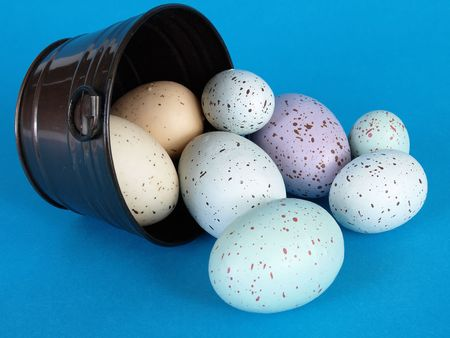 Speckled pastel colored eggs fill a metal pail, a few eggs laying to the side, over a blue background.