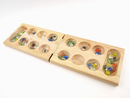 A folding wooden Mancala board game with glass stone pieces, isolated against a white background. Stock Photo