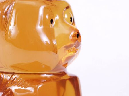 A close up of the face of a Honey bear jar isolated on a white background