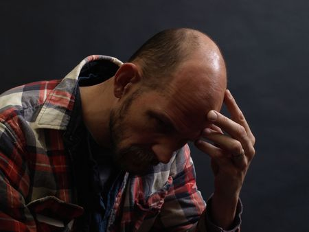 A man in deep thought holds his head in his hand. Over black.