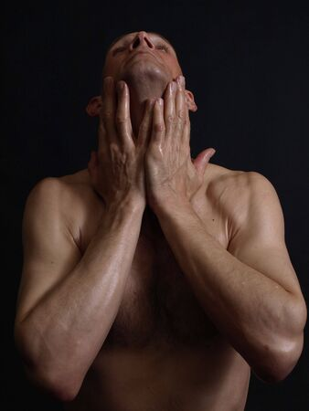A shirtless man with his hands on his neck isolated by a black background