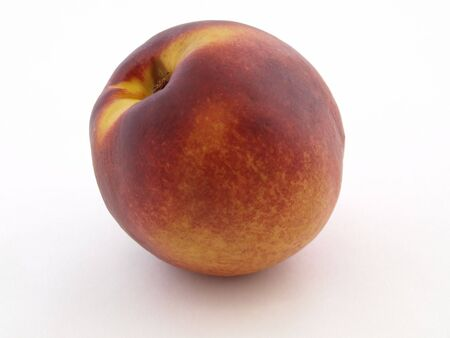 a single juicy peach isolated against a white background