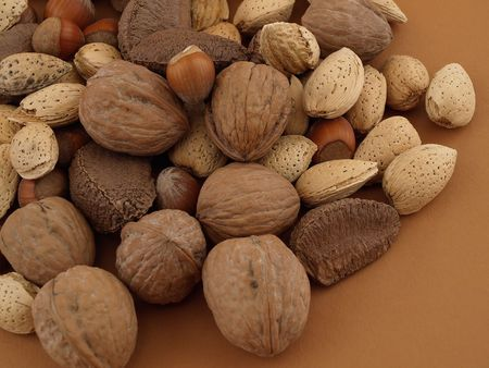 A selection of various types of nuts isolated on a brown background. Stock Photo