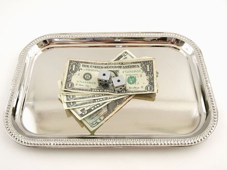 high stakes: Two dice and money on a silver tray isolated on a white background