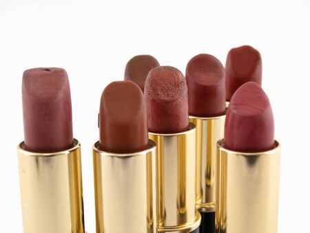 Several different red colored lipstick tubes isolated on a white background