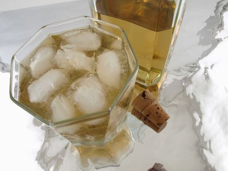 A glass on alcohol with ice, a bottle and a cork isolated on a reflective back ground