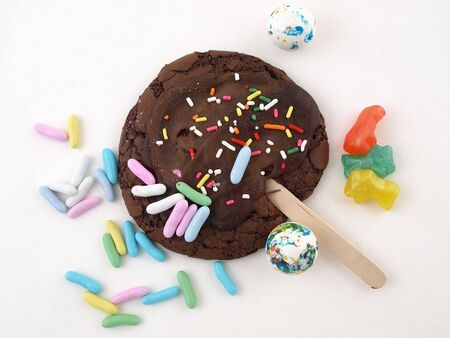gummie: A chocolate frosted cookie with sprinkes, and other colorful candies isolated on a white back ground