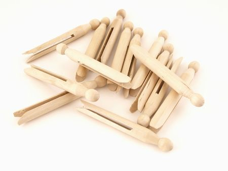 A pile of old fashioned clothespins isolated on a white background.