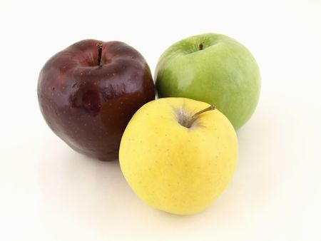 Three different colored apples in a grouping isolated on a white background