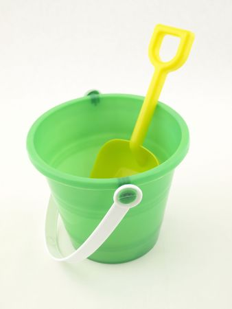 a yellow plastic shovel inside of a green bucket isolated on a white background