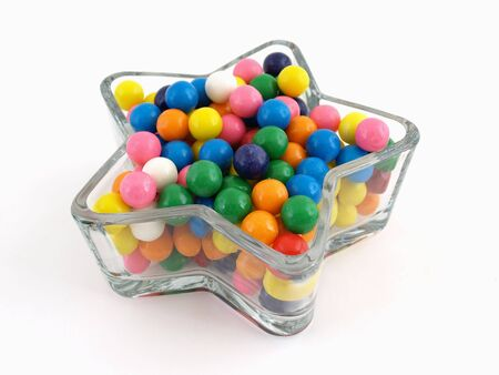 A star shaped dish filled with multi colored gumballs isolated over a white background.