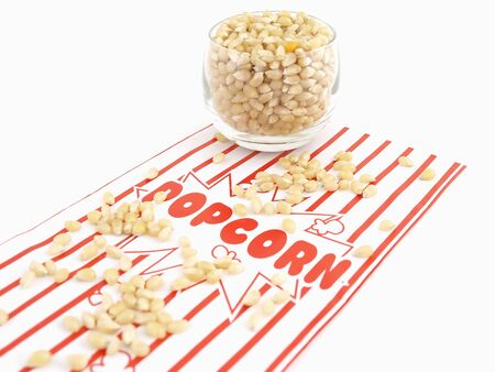 A popcorn bag and kernels isolated over a white background.