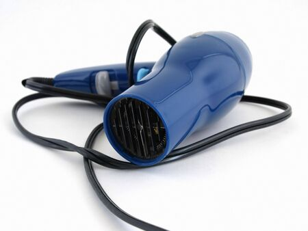 A blue hair dryer with a black cord isolated on a white background.