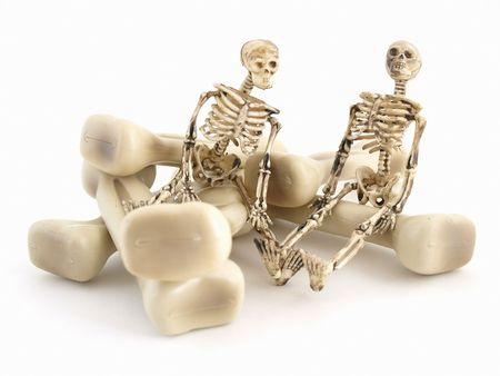 Two skeleton figures sitting on some bones isolated on a white background Stock Photo