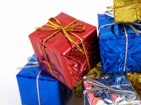 Colorful gift boxes in shiny wrapping paper isolated against a white background. Stock Photo