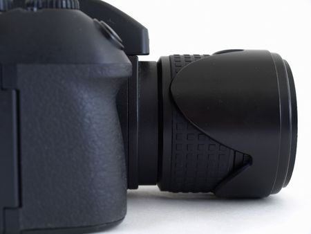 A black digital camera body with an attached lens. Studio isolated over white.