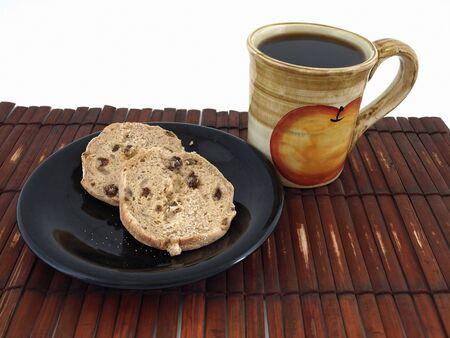 Twee chocolade chip cookies op een plaat met een kop warme koffie. Op een bamboe mat, in wit.