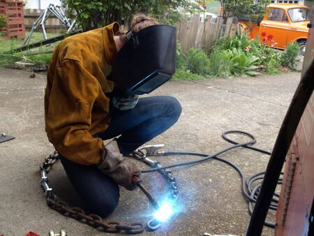A woman wearing protective gear welds a piece of chain together.