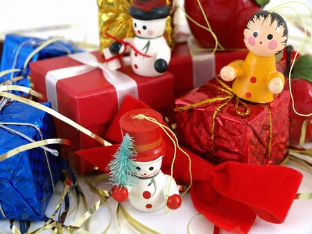 Cute colorful wooden Christmas tree ornaments, displayed with colorful wrapped presents. Over white. Stock Photo