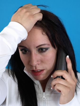 stopping: Alternative style adult woman looks stressed as she speaks into the telephone. Stock Photo