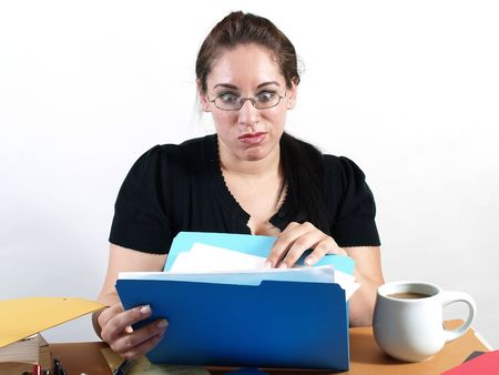 A female office worker checks a file with a worried look on her face. photo