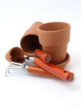 Several different sized terra cotta clay pots and gardening tools isolated on a white background.