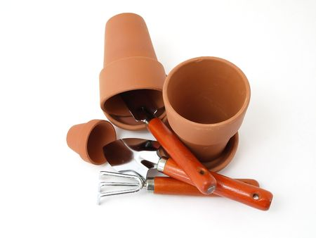 terra cotta: Several different sized terra cotta clay pots and gardening tools isolated on a white background.