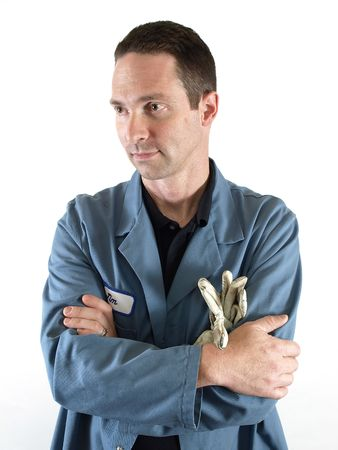 smock: A male employee in a blue lab coat stands with his arms crossed.