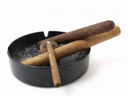 Three cigars resting in a dirty ashtray isolated on a white background. photo