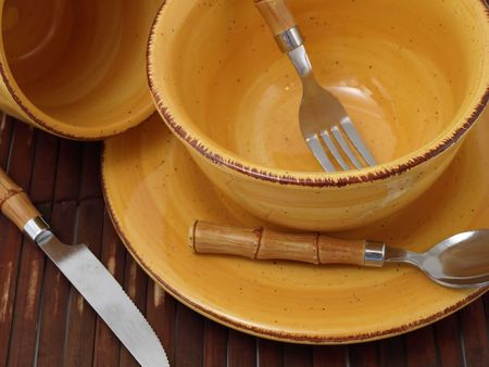 rimmed: A ceramic bowl on a plate with a cup and utensils in thick earth tones atop a brown bamboo placemat.