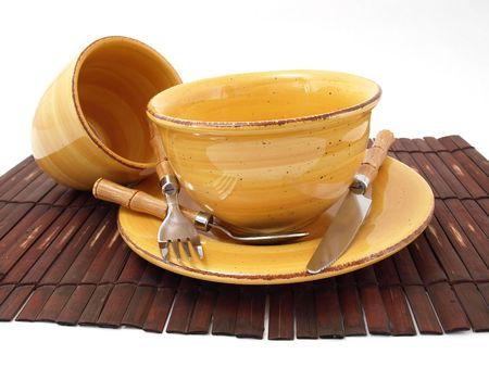 A ceramic bowl on a plate with a cup and utensils in thick earth tones atop a brown bamboo placemat. photo