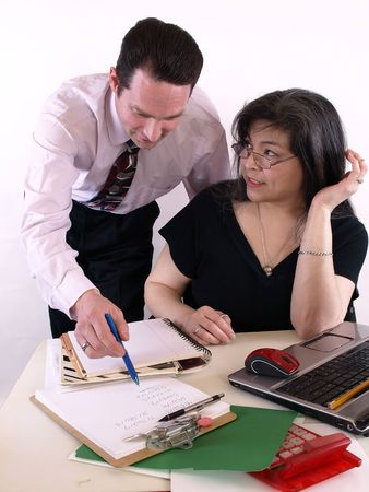 conferring: A male and female working together in the office at the computer. Isolated against a white background.