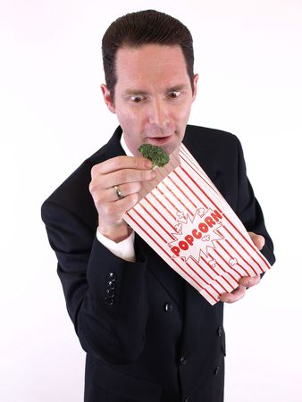 A man in a black suit pulls a piece of broccoli from a popcorn bag. Over white. Stock Photo - 4687260