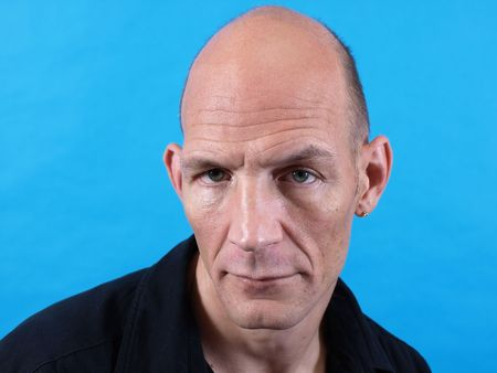A balding middle aged man isolated against a blue background.