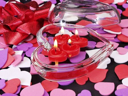 Heart shapes strewn in the background of a glass holding lit red candles Stock Photo - 4733797
