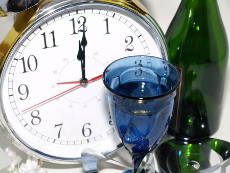 A clock reading 12:01 with a glass and a green bottle. Banco de Imagens