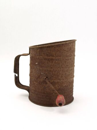 sifter: An old rusty flour sifter isolated on a white background.