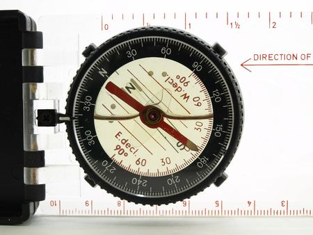 A plastic compass with a red spinner in macro over white.