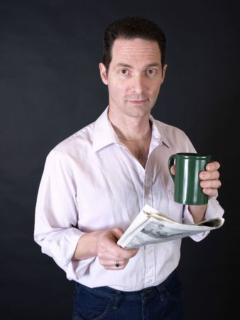 An adult man drinking coffee and reading the newspaper.