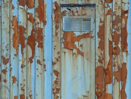 A rusty old metal building, flaking and peeling.  View of door and frame with vent.